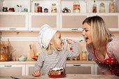 小さなかわいい女の子フィーディング彼女の母親ケーキ