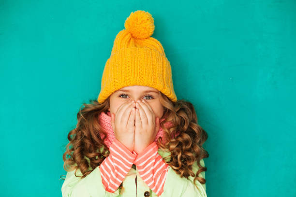 Little cute girl feeling cold Little cute amazed girl wearing warm cap and scarf feeling cold warm clothing stock pictures, royalty-free photos & images