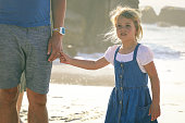Little cute girl holding her dads hand on the beach on a sunny spring day