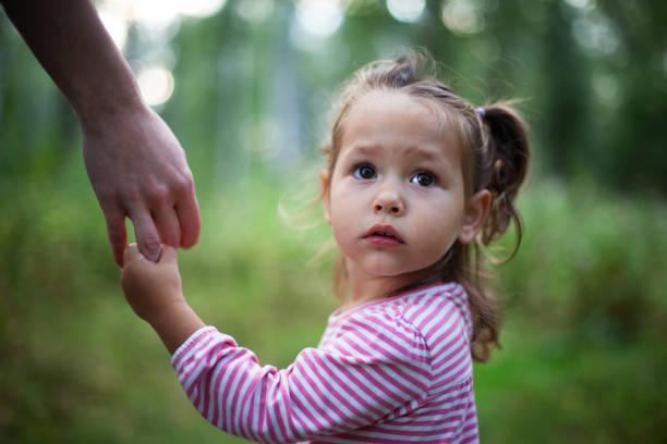 little cute girl holding mother's hand - mano donna dita unite foto e immagini stock