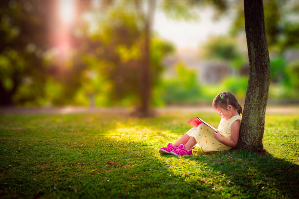 een klein schattig meisje in een gele jurk lezen van een boek, zittend onder de boom - a little girl reading a book stockfoto's en -beelden