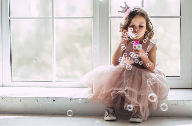 Little cute girl in dress Little cute girl in beautiful dress is sitting near the window at home and blowing soap bubbles. girls stock pictures, royalty-free photos & images