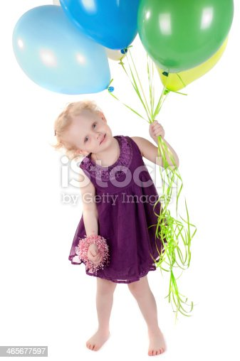 istock Little cute girl in dress with air balloons 465677597