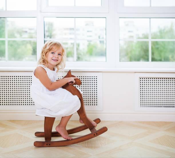 little cute girl in nursery room with wooden horse - pferde schlafzimmer stock-fotos und bilder