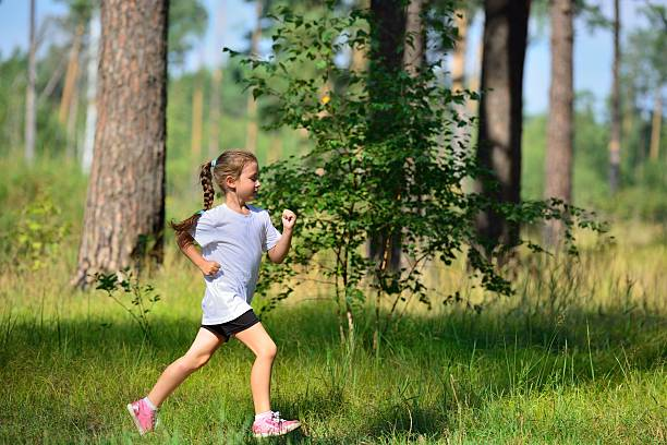 Cтоковое фото Little cute girl jogging in forest