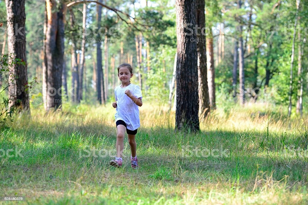 Little cute girl jogging in forest стоковое фото