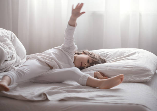 Little cute girl playing in bed , sleep concept Cute little girl playing lying in a white cozy bed , the concept of children's rest and sleep little girls in panties stock pictures, royalty-free photos & images