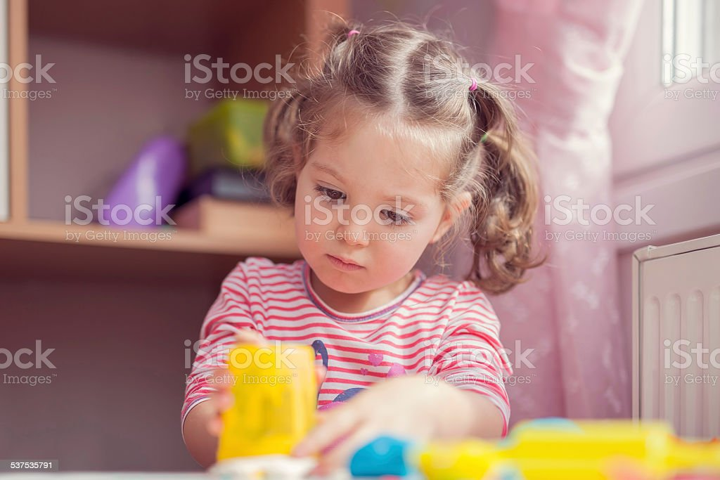 little cute girl playing in her playroom stock photo