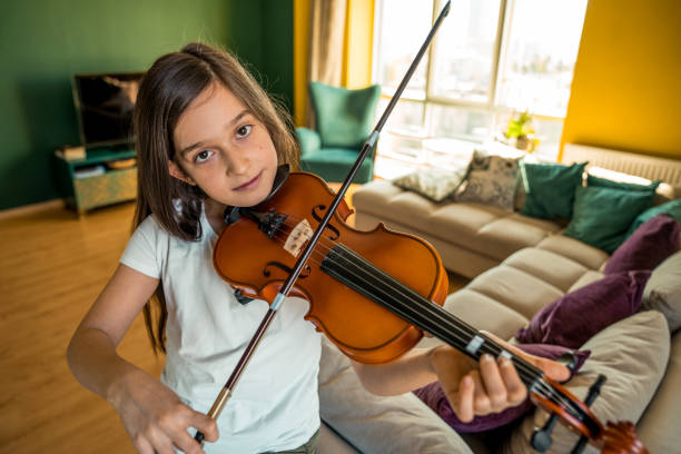 little cute girl playing violin at home stock photo