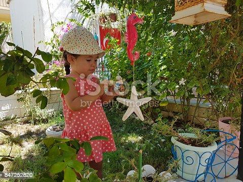 little cute girl plays with garden toys in curiosity