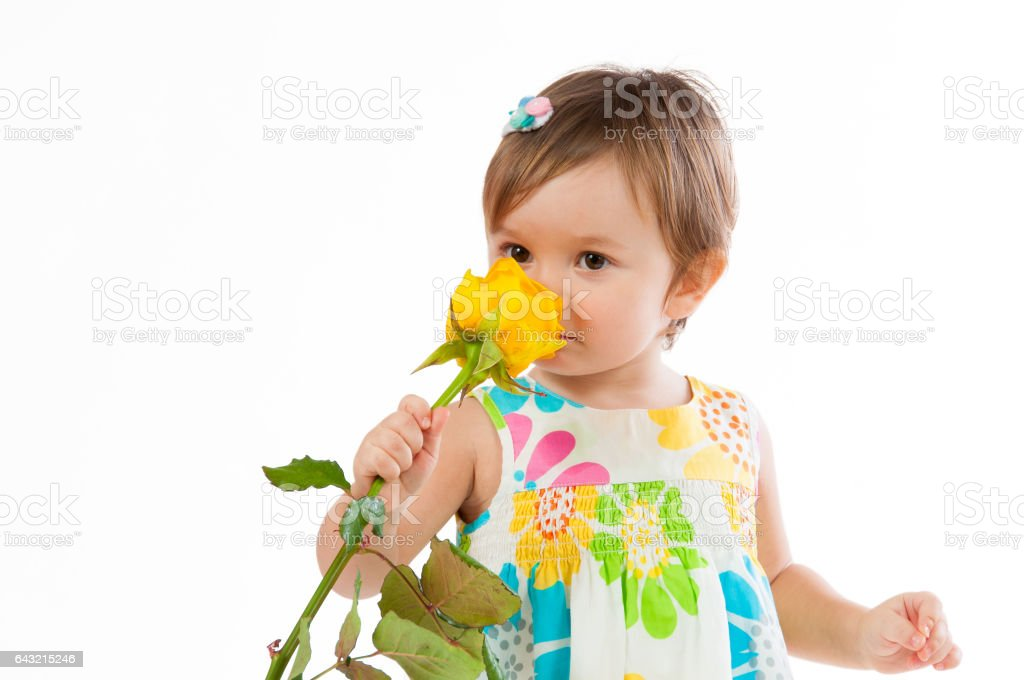 Little cute girl smelling a yellow rose, romantic gift stock photo