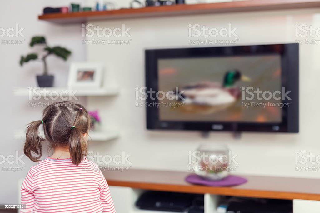 little cute girl watching tv in living room stock photo