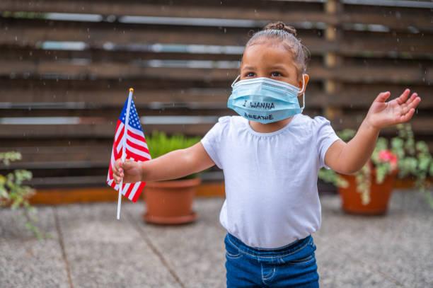Kleines süßes Mädchen trägt schützende Gesichtsmaske mit 'Ich will atmen' Handschrift darauf und hält eine kleine amerikanische Flagge – Foto
