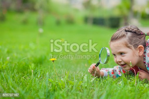 istock little cute girl with magnifying glass examining flower 525737167