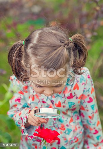 istock little cute girl with magnifying glass examining flower 525739321