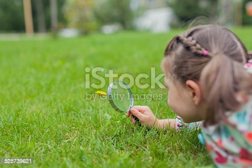istock little cute girl with magnifying glass examining flower 525739621