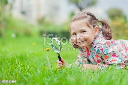 istock little cute girl with magnifying glass examining flower 525740191