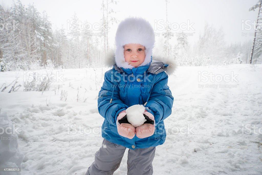 Маленькая симпатичная девушка с Снежок в руки на лес стоковое фото