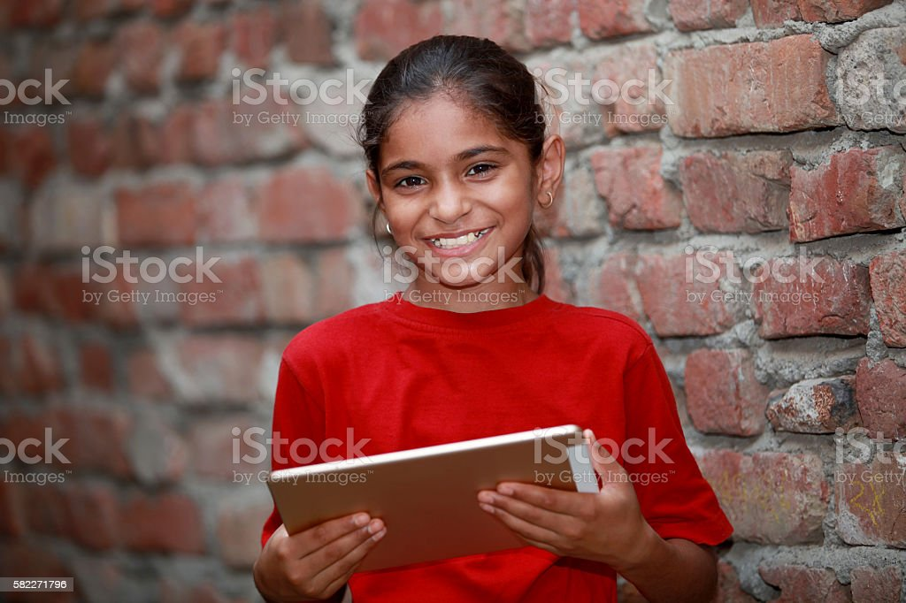 Little cute happy girl holding tablet stock photo