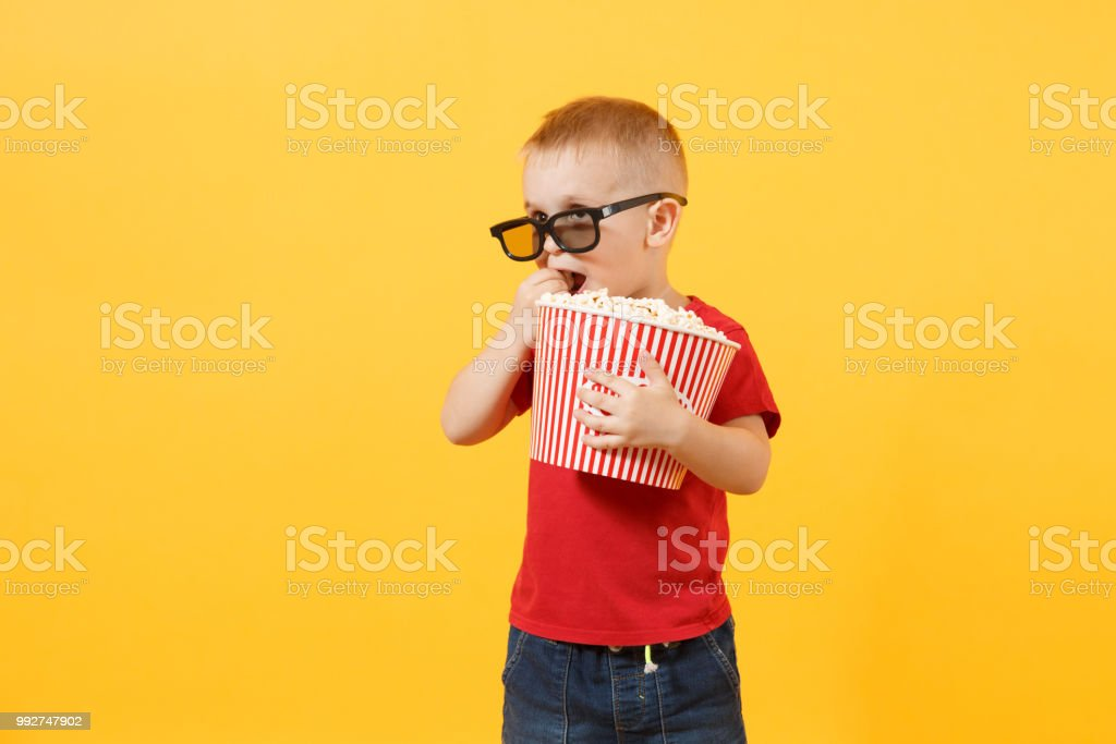 b4e1a03de9ec Little cute kid baby boy 3-4 years old in red t-shirt, 3d imax cinema  glasses holding bucket for popcorn, eating fast food isolated on yellow  background.