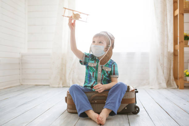 Little cute kid boy in quarantine at home dreams of traveling. stock photo