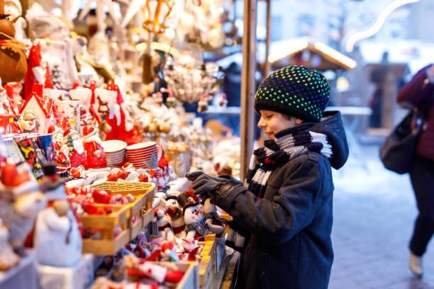 kleine süße kind junge auswahl dekoration auf dem weihnachtsmarkt. schönes kind einkaufen für spielzeug und dekorativen ornamenten - weihnachtsfeier münchen stock-fotos und bilder