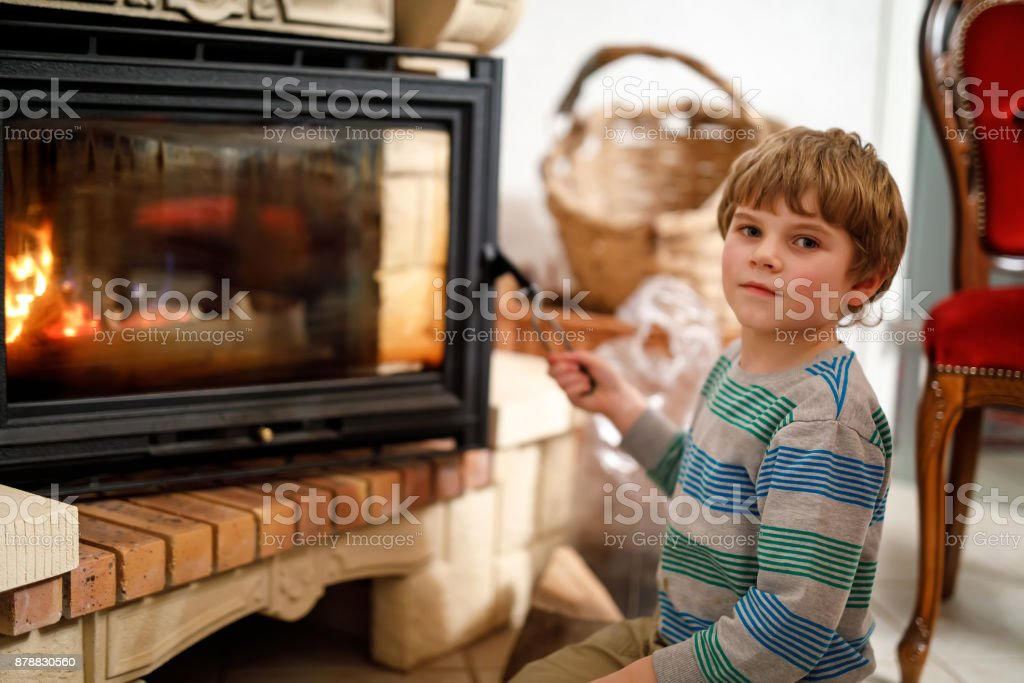Kleine süße Kind junge Kamin zu Hause sitzen und dabei Ausschau nach Feuer – Foto