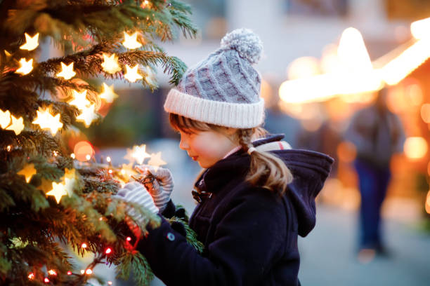 Little cute kid girl having fun on traditional Christmas market during strong snowfall. Happy child enjoying traditional family market in Germany. Schoolgirl standing by illuminated xmas tree. stock photo