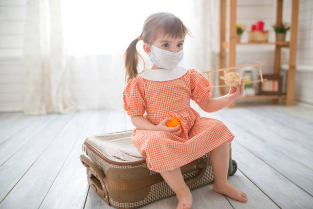 Little cute kid girl in quarantine at home dreams of traveling. stock photo