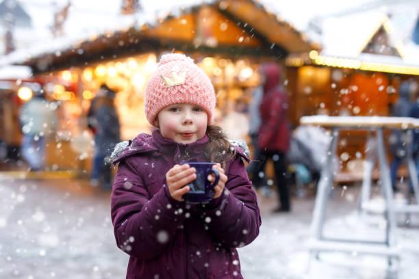 kleine süße kind mädchen mit tasse dampfenden kakao oder kinder-punsch. glückliches kind auf weihnachtsmarkt in deutschland. traditionelle freizeit für familien auf weihnachten. - stoffe berlin stock-fotos und bilder