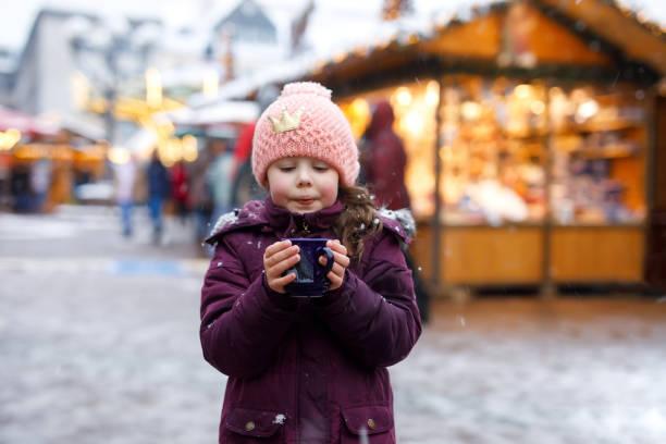 kleine süße kind mädchen mit tasse dampfenden kakao oder kinder-punsch. glückliches kind auf weihnachtsmarkt in deutschland. traditionelle freizeit für familien auf weihnachten. - weihnachtsfeier münchen stock-fotos und bilder