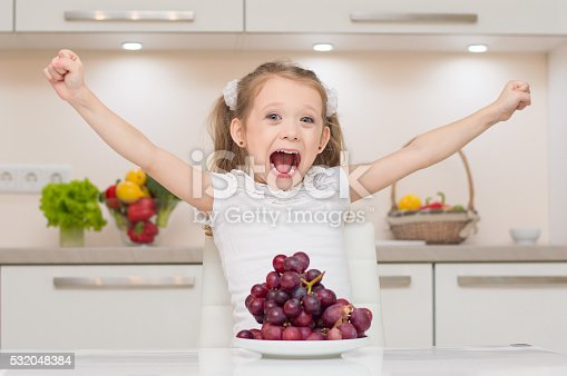 Sweet cute young positive girl with two ponytails shouts and put hands up near bowl full of fresh grapes.Little cute preschool girl in the kitchen smiles and hugs bowl full of healthy fresh vegetables - broccoli, paprika, lemons