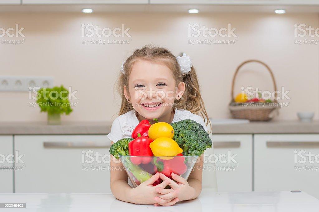 Little cute preschool girl in the kitchen stock photo