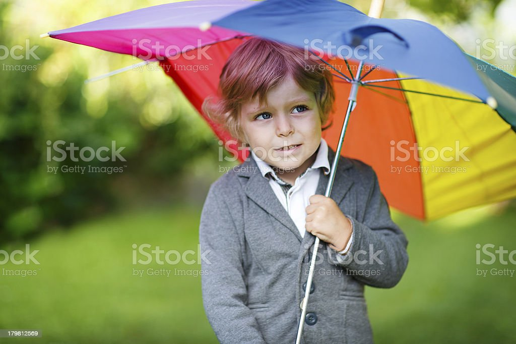 Little cute toddler boy with colorful umbrella and boots, outdoo royalty-free stock photo