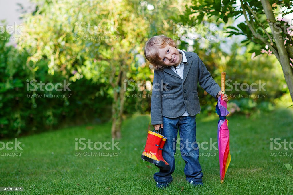 Little cute toddler boy with colorful umbrella and boots, outdoors royalty-free stock photo
