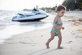 little cute toddler kid runs along the sea beach on a sunny warm day..