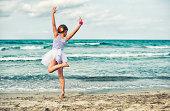 Little girl dancing ballet on the beach.