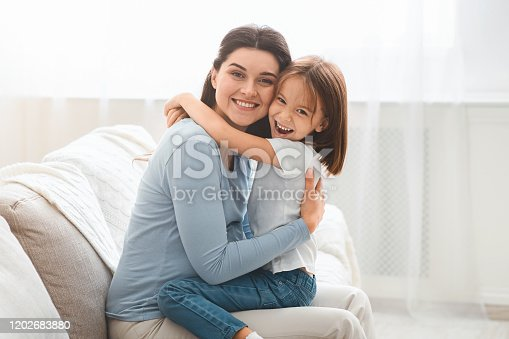 Happy little daughter and young mother hugging each other at home, sitting at living room