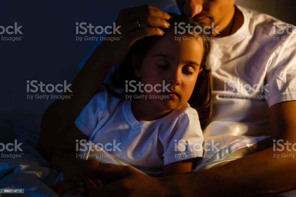 Little daughter fell asleep at the father while reading the book stock photo