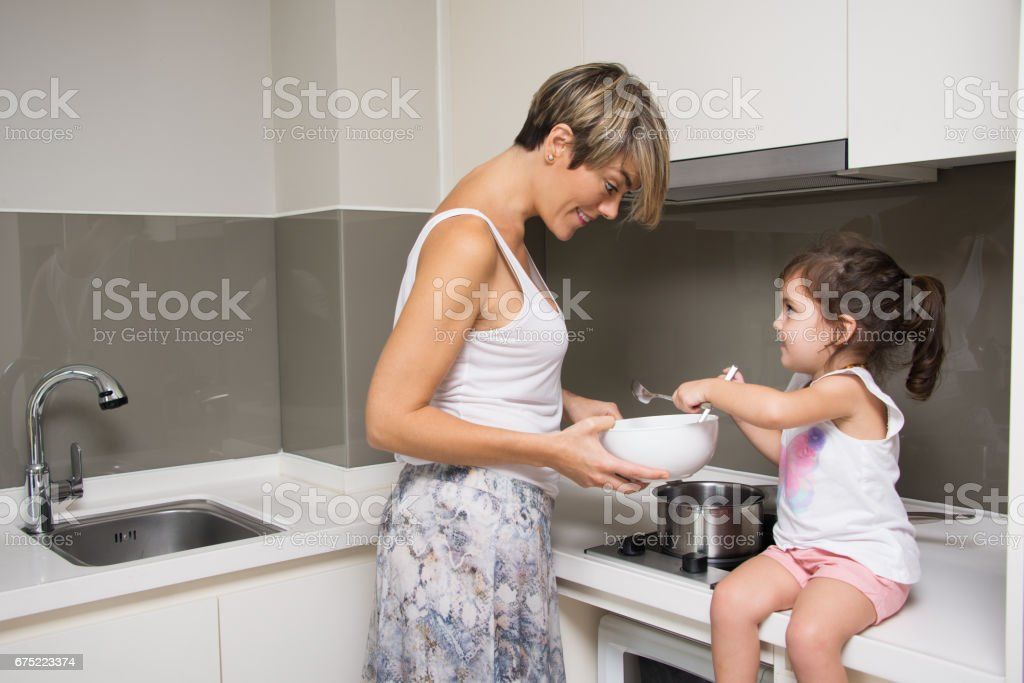 Little daughter helping mom at kitchen royalty-free stock photo