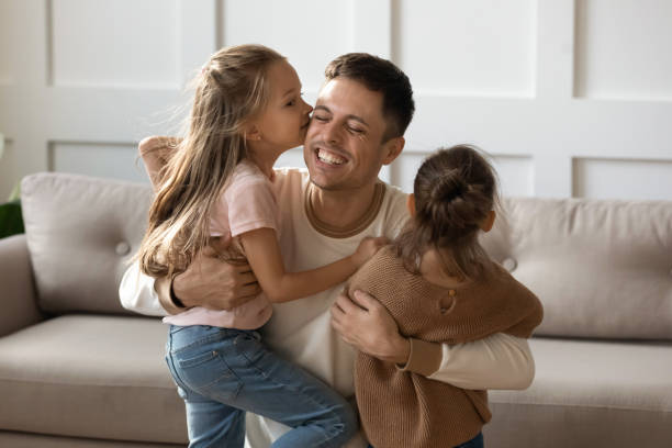 Little daughters kiss on cheeks happy young father Loving cute preschooler girls kids kiss young father on cheeks showing affection and care, happy little daughters hug and cuddle smiling Caucasian dad, enjoy share tender family moment at home little girl kissing dad on cheek stock pictures, royalty-free photos & images