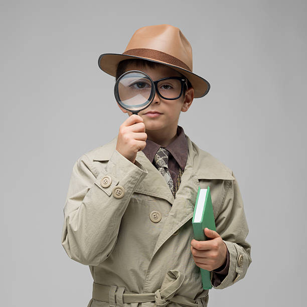 little dedective looking through magnifying glass on gray background - sherlock holmes stock photos and pictures