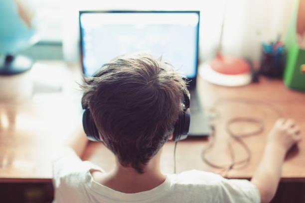abhängigen gamer geißlein spielen auf laptop - schulkind nur jungen stock-fotos und bilder