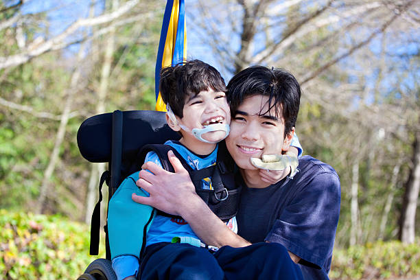 Little disabled boy in wheelchair hugging older brother outdoors stock photo