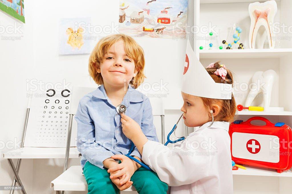 Little doctor examining boy with stethoscope stock photo