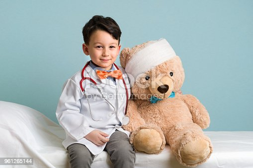 The cute child is acting like a doctor and he is examining his teddy bear.