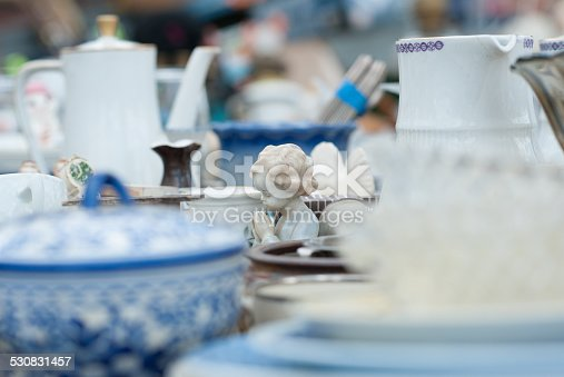 A little doll of china is sitting alone on a flea market table praying with hands together and eyes closed