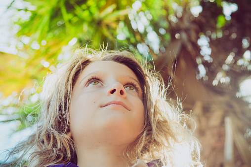 Sweet little girl in a outdoor portrait in a tropical sunny location. Her eyes look up to the heavens. Lush foliage, summer daydreaming outdoors