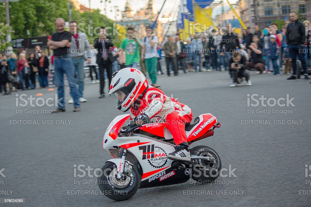 Little driver demonstrates management skills motorcycle. Kiev, Ukraine stock photo