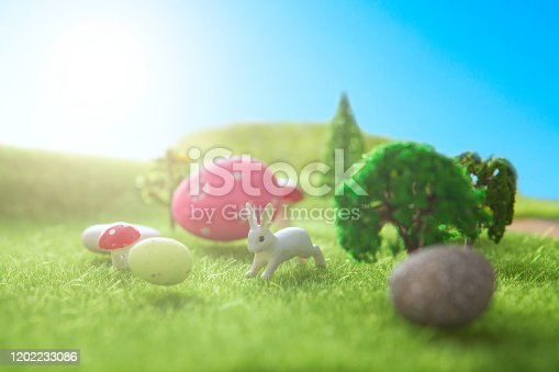 Little Easter bunny toys and Easter eggs on a green grass. Fairy tale